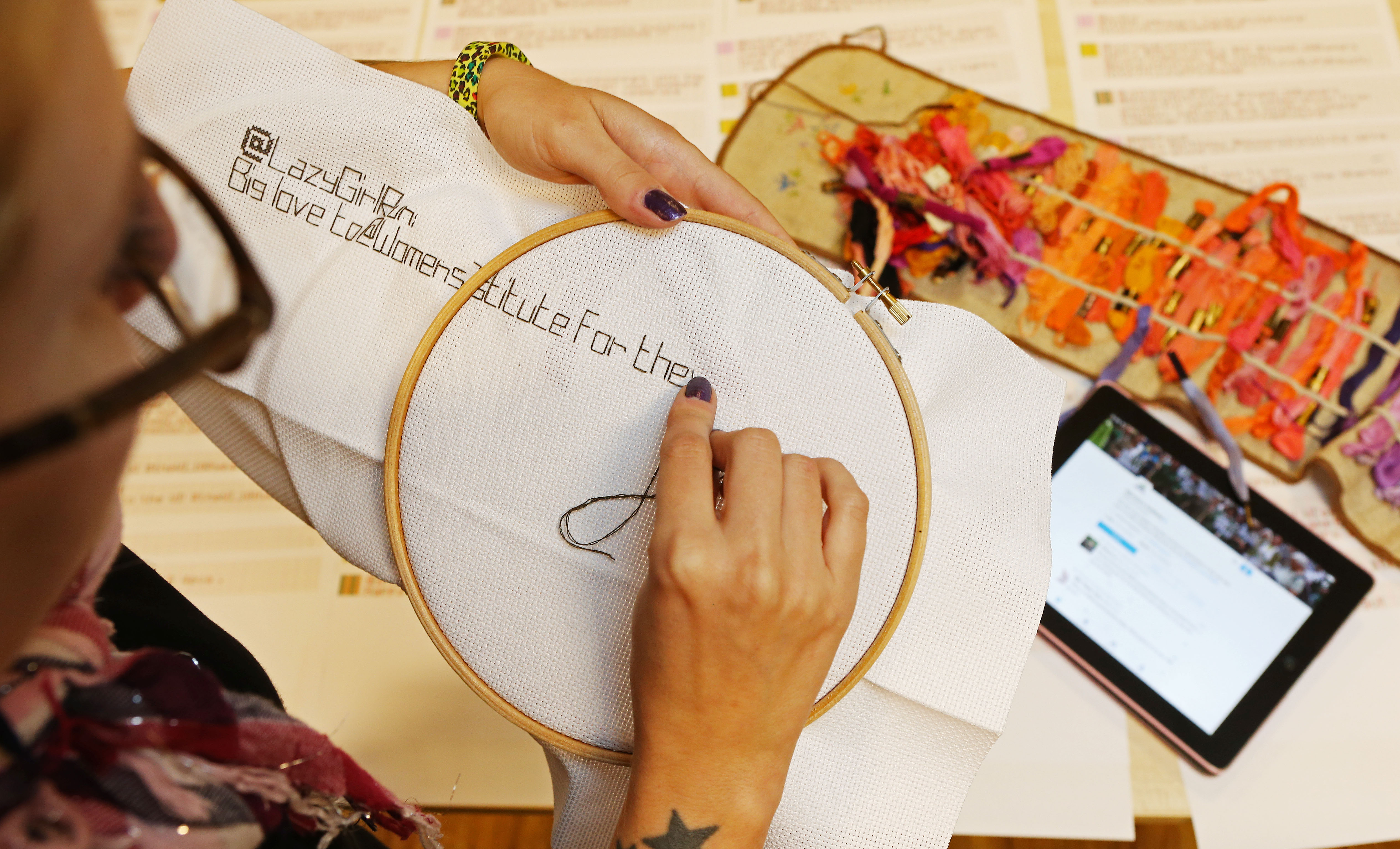 Mandatory Credit: Photo by Joe Pepler/REX Shutterstock (5086417e) A member of the WI stitches a twitter message onto canvas WI Twitter live-stitching, Women's Institute Headquarters, London, Britain - 16 Sep 2015 The National Federation of Women's Institutes is celebrating its centenary in 2015. As part of the celebrations, and to bridge the gap between the traditional reputation of the WI and the modern digital age, the Institute held a 'tWItterstitch' live event.  During the event, a group of WI members live-stitch anniversary wishes that are received via Twitter by both manually cross-stitching and machine stitching the messages. The tweets are then auto-printed onto a sewing pattern as they are received and handed to one of the stitching team to be committed to canvas. Each individual stitched tweet is added to a large wall hanging, which will be put on display at the NFWI headquarters to provide a lasting legacy of the online buzz around the centenary.