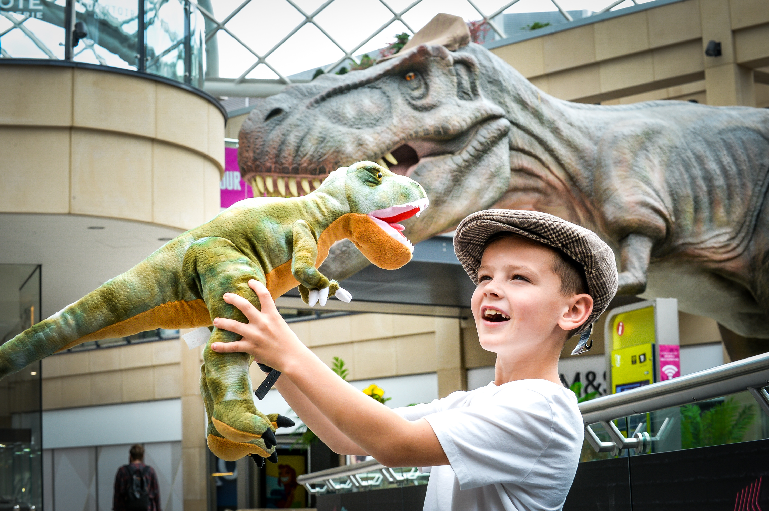 Trinity Leeds visitor and the flat cap wearing T-Rex dressed up for the part.